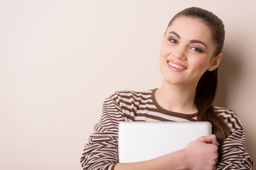 young woman standing and holding laptop.