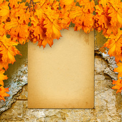 Old paper listing on old brick wall with bright orange autumn le
