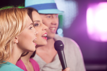 Happy three friends singing in microphones.