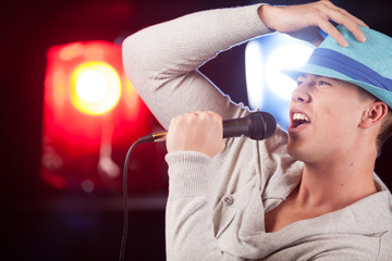 handsome guy holding mic and singing.