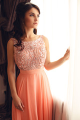beautiful woman in elegant coral dress with diadem