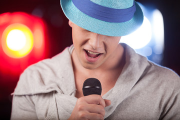 Portrait of male singer wearing blue hat.