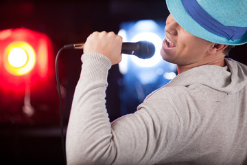 back view of male singer wearing blue hat.