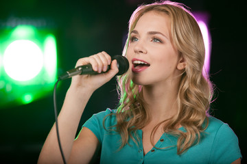 Portrait of young beautiful girl singing.