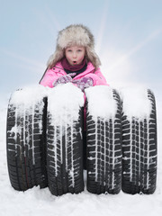 Blond child with tyres in the snow