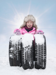 Child with tyres in the snow