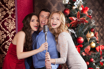 Photo of three frienda singing at party.