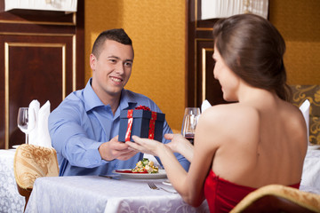 Smiling attractive man giving woman present.