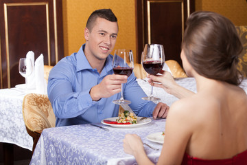 Smiling attractive man drinking wine with woman.