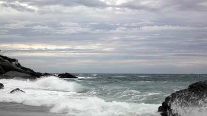 Beach on the Ligurian Sea early in the morning in cloudy weather