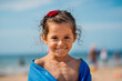 Smiling portrait of young girl on the beach with towel.