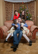 father kissing daughters on sofa at christmas eve