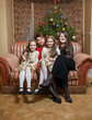 mother with daughters sitting on sofa at christmas eve
