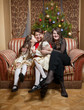 happy daughters sitting on sofa with mother at christmas