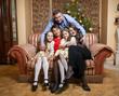 father hugging big family seated on sofa at christmas day
