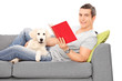 Man lying on sofa with puppy and reading a book