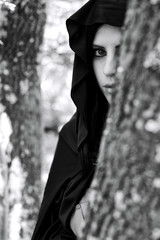 Portrait of woman with hood hiding in forest