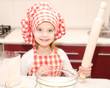 Smiling little girl with chef hat and rolling  pin