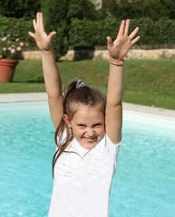 Bambina con le braccia alzate vicino alla piscina