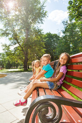 Several kids sitting on the bench in summer park