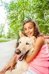 Nice girl hug her dog sitting on the bench