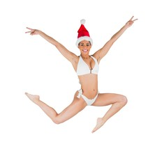 Fit girl in bikini smiling at camera wearing santa hat