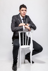 elegant man in suit sitting on wooden chair at studio