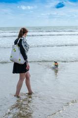 femme à la mer, avec un chien, bulldog français, plage