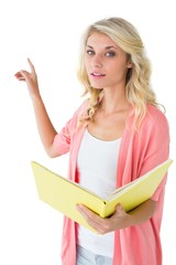 Pretty young blonde holding book and pointing