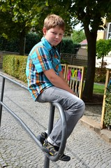 Junge sitzt auf Geländer