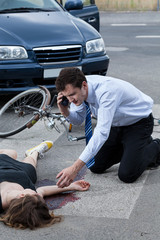 Man calling an ambulance for injured woman
