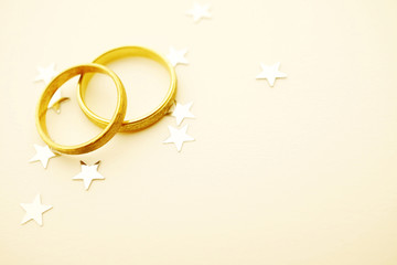 Gold wedding rings with stars on paper
