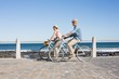 canvas print picture - Happy casual couple going for a bike ride on the pier