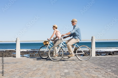 canvas print picture Happy casual couple going for a bike ride on the pier