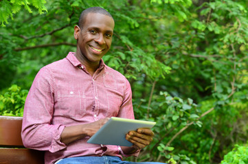Happy guy using his tablet pc, outdoors