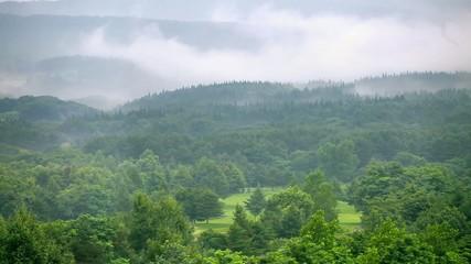 蒸気の立ち込めるゴルフ場と山