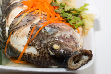 A Steamed Tilapia fish garnish with vegetables