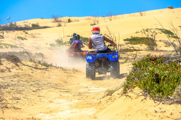 Two quads racing after one another in deserted dusty areas