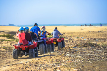A caravan of three quads driving towards the sea