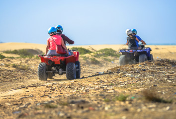 Two teams racing on quads towards the sea
