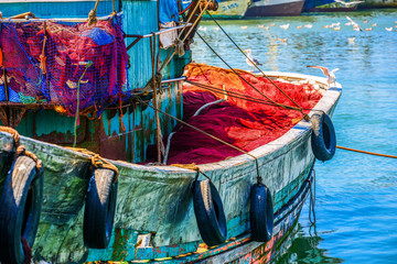 Colorful fishing boat with seagulls sitting on the sideboard