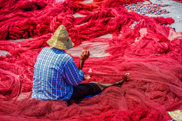A man sewing fishing nets