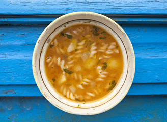 Vegetables soup with pasta on blue background
