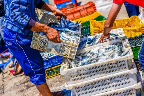 Keuken foto achterwand Boodschappen Fishermen arranging containers with fish