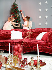 Two girls as angels decorate the Christmas tree