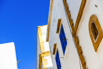 White wall with blue windows and yellow frames