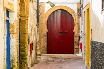 A beautiful arched red door at the end of a narrow street