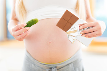 Pregnant woman holding pickle and chocolate