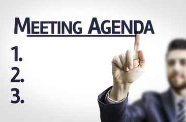 Business man pointing the text: Meeting Agenda