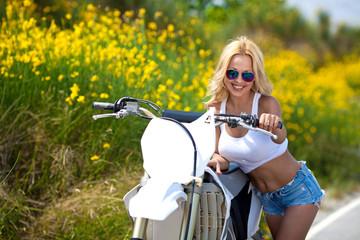 Красивая девушка возле мотоцикла на дороге летом
